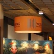 Grote lampenkap boven beursstand, bedrukt met WESTAG logo